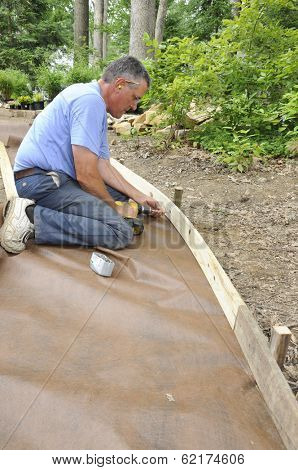Man installing gravel path