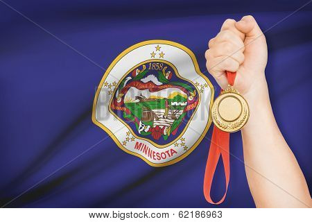 Medal In Hand With Flag On Background - State Of Minnesota. Part Of A Series.