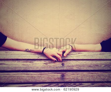 two people holding hands on a bench done with a retro vintage instagram filter