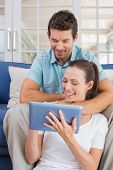 Happy young couple using digital tablet on couch at home poster