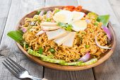 Dry Instant Noodle, Malaysian style maggi goreng mamak or spicy dry curry instant noodles. Asian cuisine, ready to serve on wooden dining table setting. Fresh hot with steamed smoke. poster