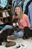 happy teen in her room, with puppies, shoes, and clothes poster