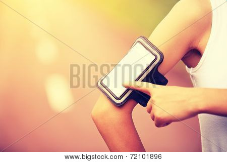 Runner athlete listening to music from smart phone mp3 player smart phone armband.