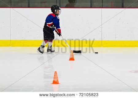 Child Practices Stickhandling At Ice Hockey Practice