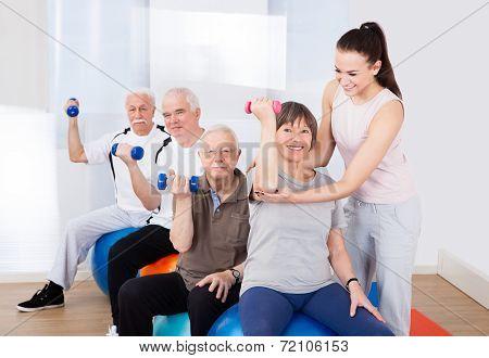 Trainer Assisting Senior People At Healthclub