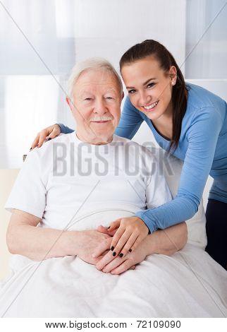 Caretaker With Senior Man At Nursing Home