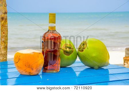 coconuts and liquor bottle on table by the beach in livingston guatemala