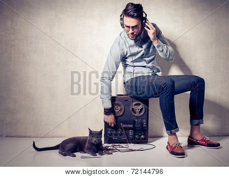 Handsome Man And Cat Listening To Music On A Magnetophone Against Grunge Wall