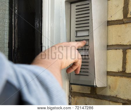 Man Ringing An Intercom To Gain Access