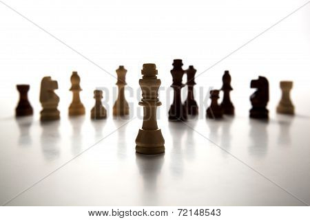 Chess Pieces Lined Up In A Row On A Gray