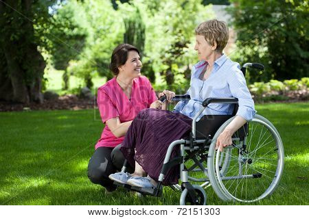 Happy senior woman on wheelchair with caring caregiver outdoors poster