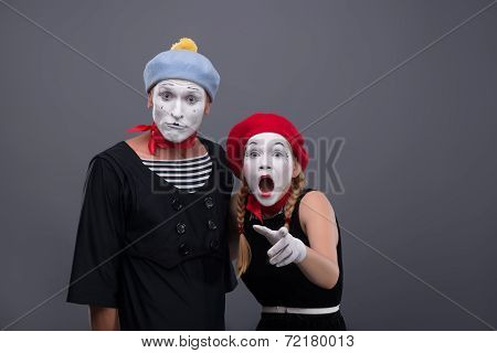 Waist-up portrait of scared mime couple looking at the camera, female mime loudly crying and showing at you, isolated on grey background with copy place poster