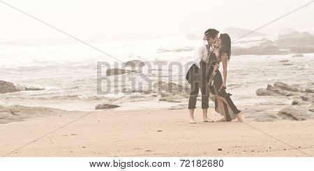 Young attractive couple walking along beach