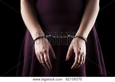 Submissive Woman Wearing A Purple Dress In Metal Handcuffs On Black Background