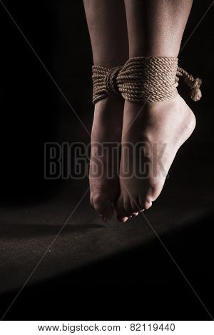 detail suspended bound feet submissive young girl on a black background / BDSM theme poster