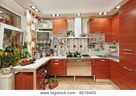 Kitchen Interior With Wooden Furniture And Many Utensils