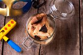 Traditional jewish Hamantaschen cookies for Purim festival with wooden rattle and carnival mask on a wooden table poster