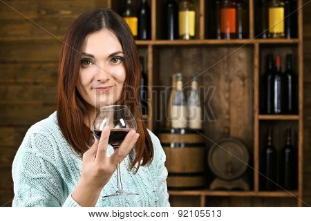 Young woman tasting wine in cellar poster