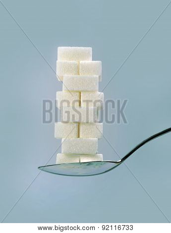 spoon with stack of sugar cubes piled in sweet excess unhealthy nutrition diet and sugar addiction concept isolated on blue background poster