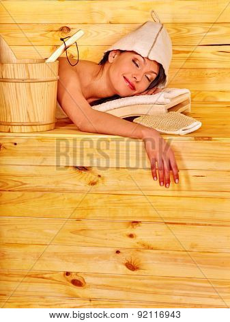 Young woman lying in sauna. Overheating danger.