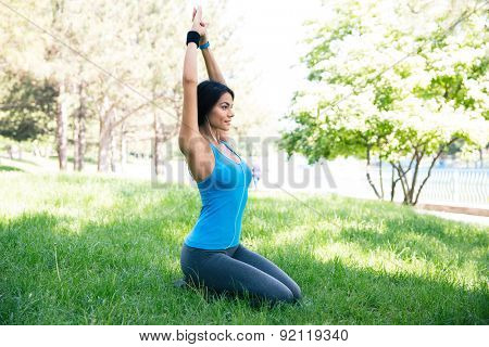 Beautiful woman doing yoga exercises on the green grass in park