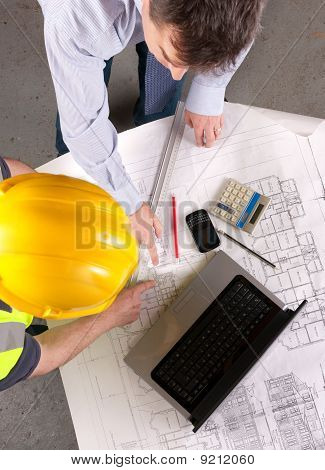 Two Men Discuss Building Plans