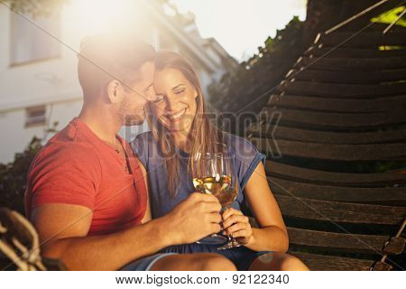 Beautiful Young Couple On Hammock Toasting Wine.