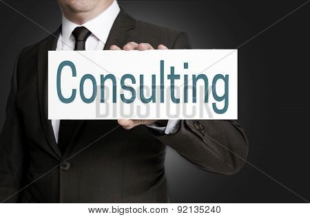 Consulting Sign Is Held By Businessman