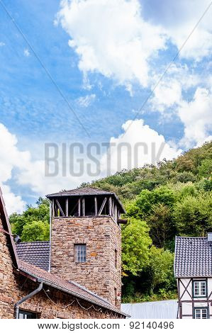 Ancient Tower And In The Background A Forest And Beautiful Blue Sky