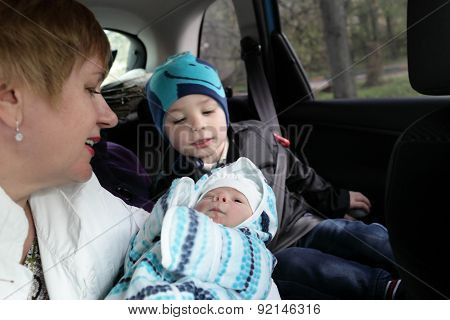 Family With Newborn Baby In Car
