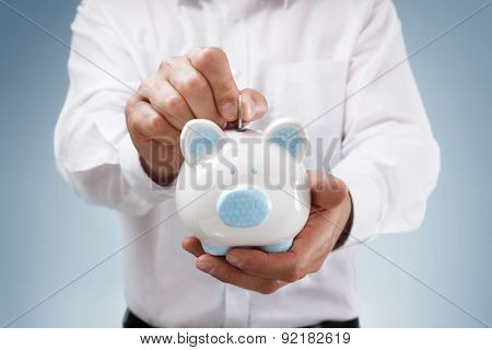 Businessman inserting a coin into a piggy bank concept for business savings, investment or banking