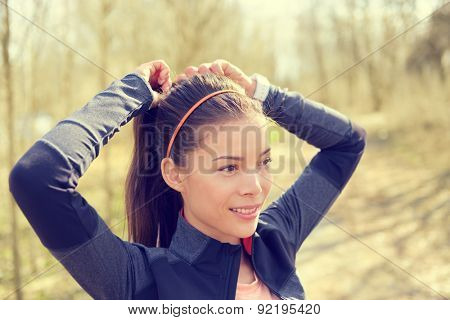 Woman tying hair in ponytail getting ready for run. Beautiful Asian young adult attaching her long brown hair on outdoor trail running path in forest to prepare for workout.
