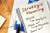Notepad with  Strategic planning concept on a wooden board. poster