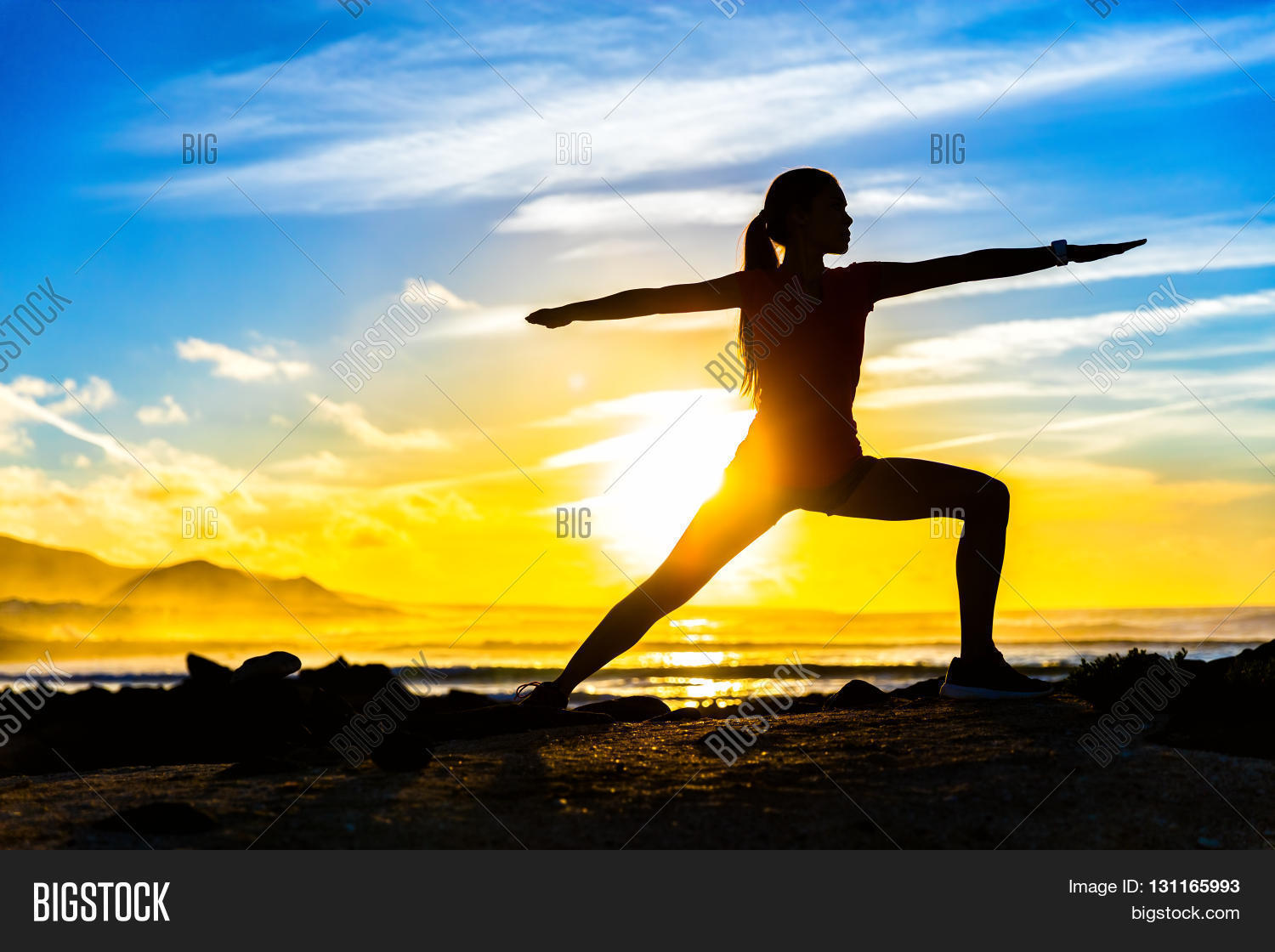 Silhouette Of Fitness Athlete Practicing Warrior II Yoga Pose Meditating At Beach Sunset Woman Stretching
