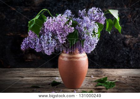 bouquet of lilac in a vase of different colors on the background of wooden walls dark colours