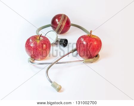 Two Apples a Stethoscope and a Duece ball.Health for sports concept.