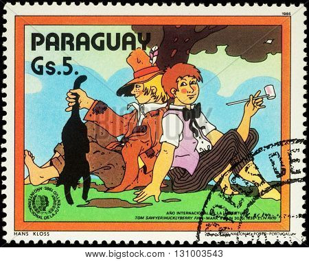 MOSCOW RUSSIA - MAY 23 2016: A stamp printed in Paraguay shows Tom Sawyer and Huckleberry Finn are sitting under a tree series