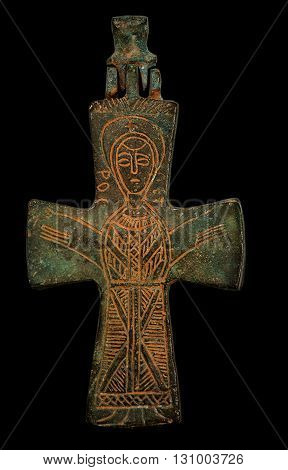 Ancient copper cross with sain image isolated on black closeup shot