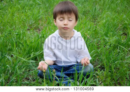 Caucasian cute boy sitting in meditation pose outside on the grass