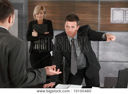 Executive firing employee in office, pointing out of frame.