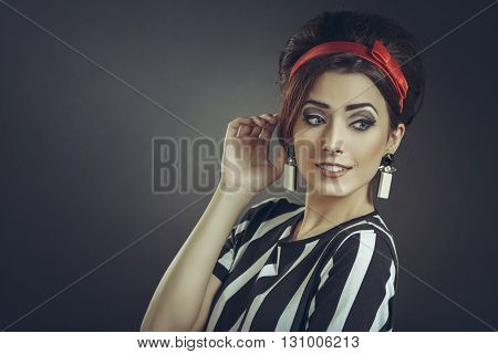 Beautiful smiling woman with hand to ear wearing striped apparel red headband and retro updo hairstyle eavesdrops on fashion rumors news or trends gossips over dark background with copy space.