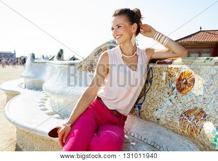 Happy Young Woman Sitting On The Famous Trencadis Style Bench