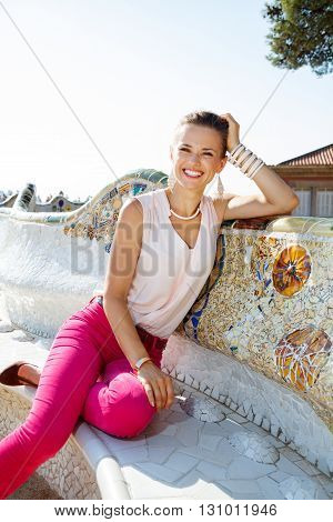Smiling Young Woman Relaxing On The Famous Trencadis Style Bench