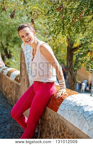 Smiling Woman Sitting On Trencadis Style Fence In Park Guell