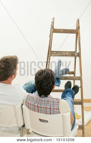 Couple relaxing after work, looking at freshly painted white wall, sitting with feet up on ladder.