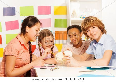 Four smiling multi ethnic teenagers studying structure of cerebrum, sitting at the desk at the anatomy lesson