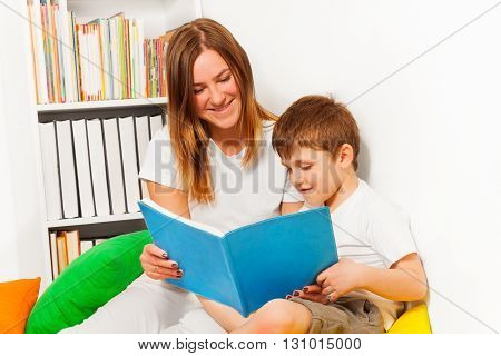 Smiling woman teaching her kid boy to read, sitting against bookcase at the room