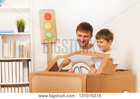 Happy kid boy and his dad, driving toy hand made cardboard car at the room