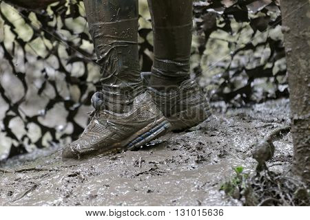STOCKHOLM SWEDEN - MAY 14 2016: Shoes in the mud camo net in the background in the obstacle race Tough Viking Event in Sweden April 14 2016