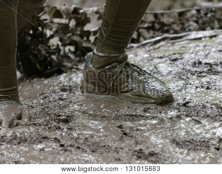 STOCKHOLM SWEDEN - MAY 14 2016: Shoe and a hand in the mud in the obstacle race Tough Viking Event in Sweden April 14 2016